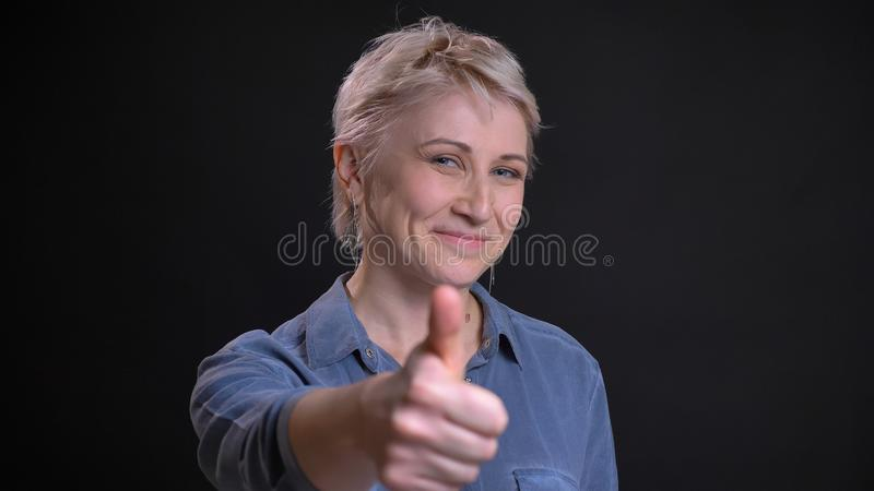 Retrato del primer de la hembra caucásica atractiva adulta que sonríe alegre y que gesticula el pulgar para arriba mientras que m foto de archivo