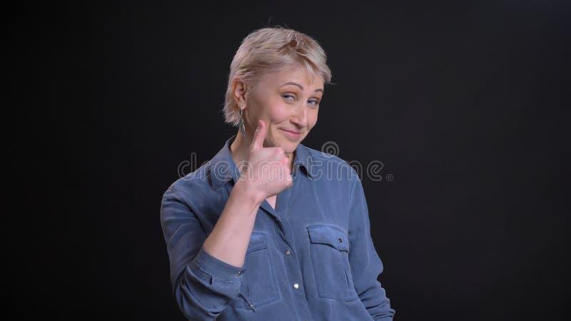 Retrato del primer de la hembra caucásica atractiva adulta que sonríe alegre y que muestra el pulgar para arriba mientras que mir imagenes de archivo