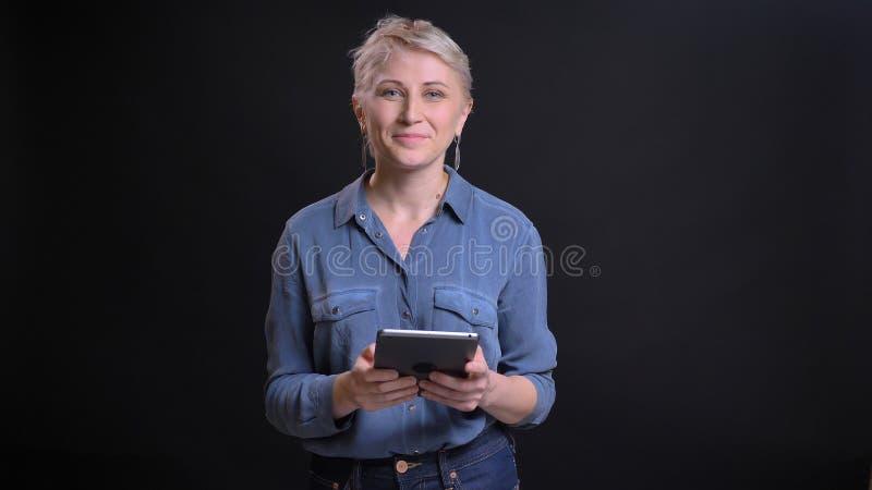 Retrato del primer de la hembra caucásica bonita adulta con el pelo rubio corto usando la tableta que mira la cámara y la sonrisa foto de archivo libre de regalías