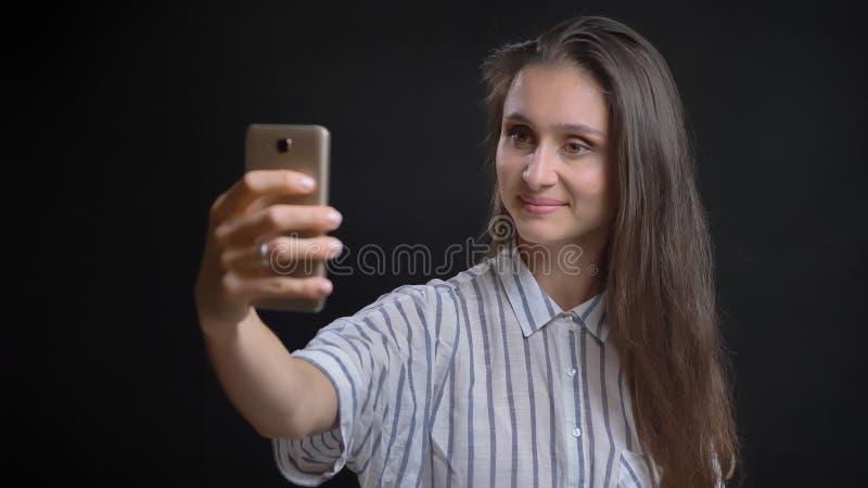 Retrato del primer de la hembra caucásica bonita joven que toma selfies en el teléfono y que sonríe delante de la cámara con imagenes de archivo