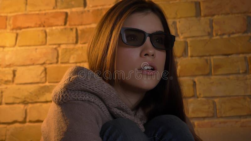 Retrato del primer de la hembra caucásica linda joven que mira una película en la TV en los vidrios 3D que son curiosos y asustad imagenes de archivo