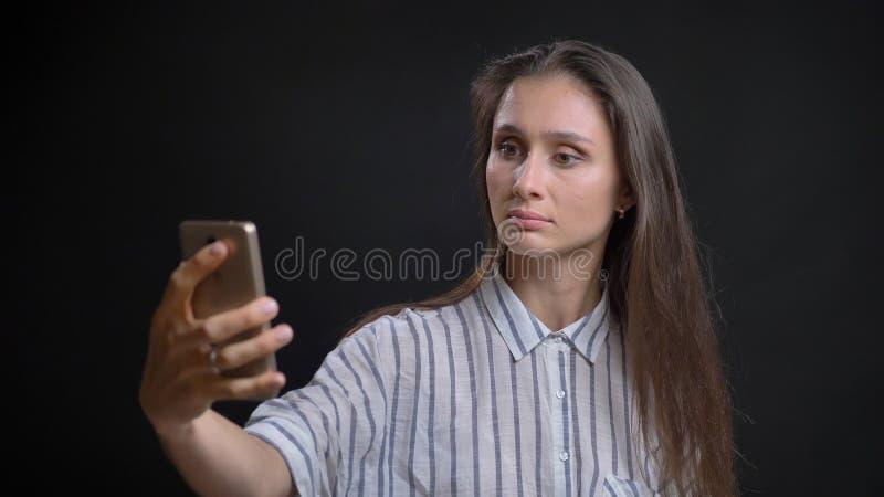 Retrato del primer de la hembra caucásica linda joven que toma selfies en el teléfono delante de la cámara con aislado imagen de archivo