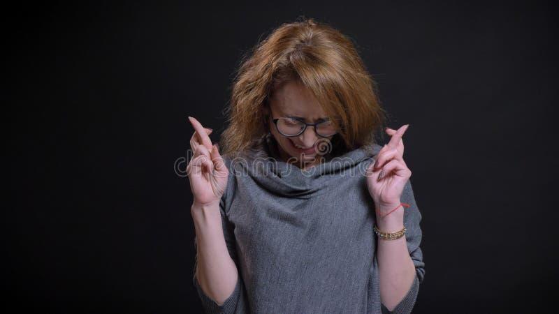 Retrato del primer de la hembra extravagante de mediana edad del pelirrojo en los vidrios que hacen sus fingeres cruzar en espera fotos de archivo