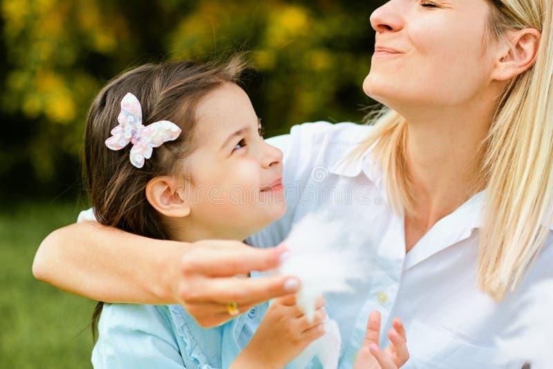 Retrato del primer de la hija feliz que come el caramelo de algodón con su madre que se sienta en la hierba en el parque D?a de m imagenes de archivo