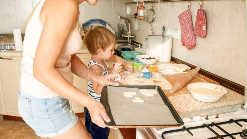 Retrato del primer de la madre joven que enseña a su hijo del niño que hace las galletas Niño con los postres de la hornada del p imagen de archivo