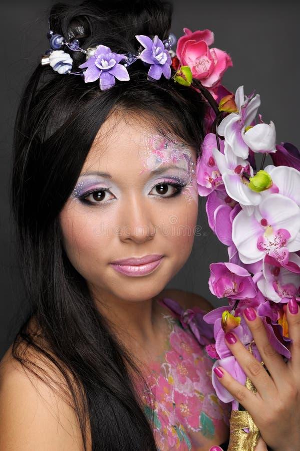 Retrato del primer de la muchacha asiática con las flores imagen de archivo libre de regalías