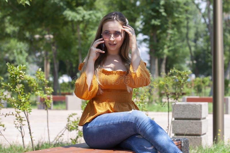 Retrato del primer de la muchacha atractiva en vidrios que habla en el tel?fono Retrato al aire libre una mujer joven rubia que h fotos de archivo