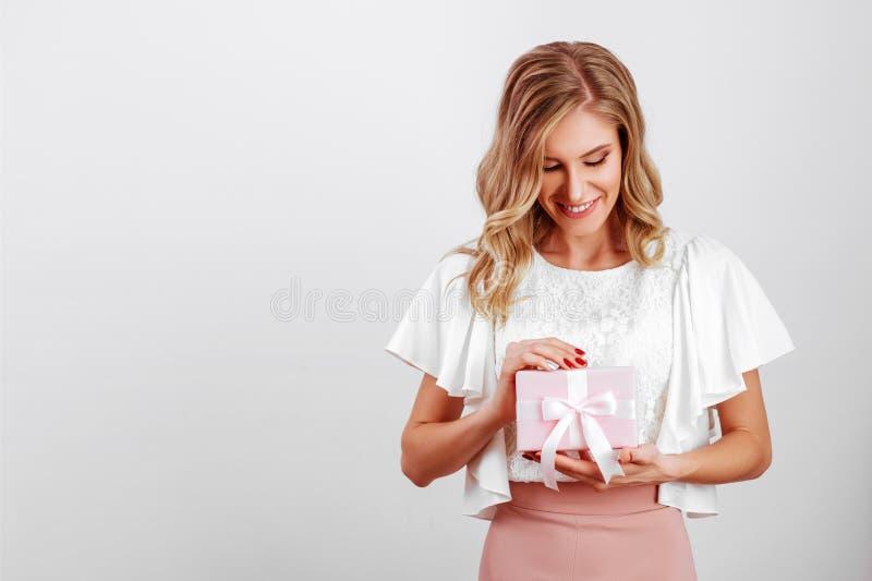 Retrato del primer de la muchacha linda con la caja de regalo rosada imagen de archivo