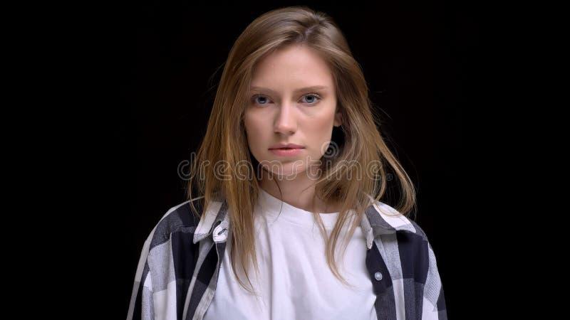 Retrato del primer de la muchacha morena caucásica hermosa joven que mira derecho la cámara con el fondo aislado en negro foto de archivo libre de regalías
