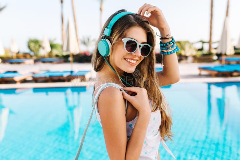Retrato del primer de la muchacha tunned con sonrisa tímida, caminando por la piscina azul en auriculares brillantes grandes Muje imágenes de archivo libres de regalías