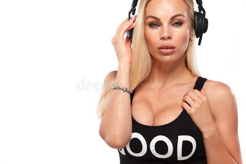 Retrato del primer de la mujer atractiva hermosa de DJ del blonde en el fondo blanco en auriculares que llevan del estudio foto de archivo