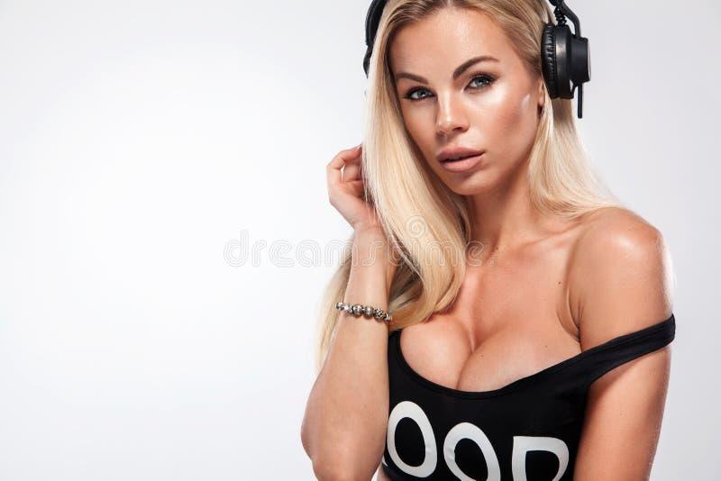 Retrato del primer de la mujer atractiva hermosa de DJ del blonde en el fondo blanco en auriculares que llevan del estudio fotografía de archivo