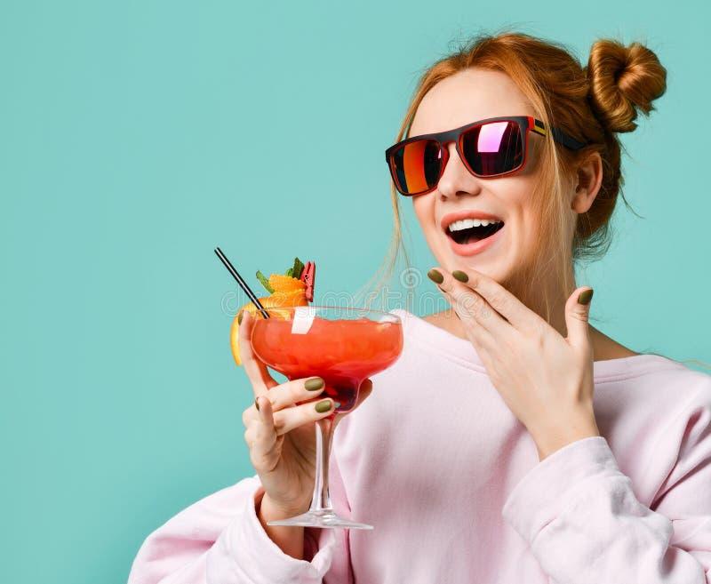Retrato del primer de la mujer del camarero con el cóctel del margarita de la fresa a disposición en gafas de sol rojas imagenes de archivo