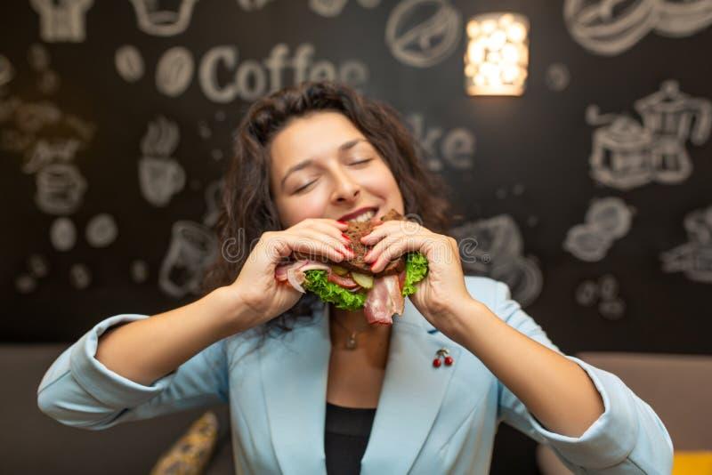 Retrato del primer de la mujer caucásica joven hambrienta, bocadillo de la mordedura fotografía de archivo