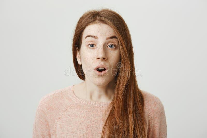 Retrato del primer de la mujer caucásica del pelirrojo hermoso que expresa choque o sorpresa, mirando con las cejas levantadas y imagenes de archivo