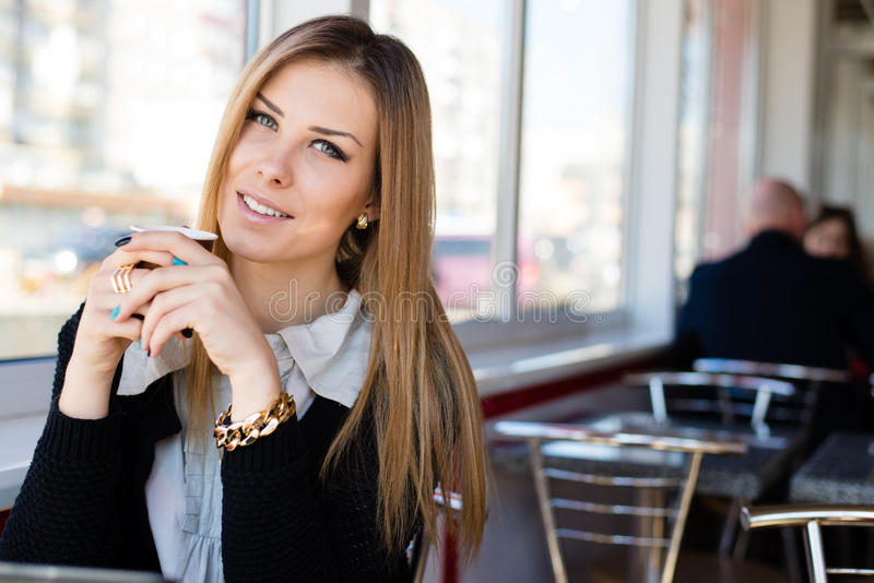 Retrato del primer de la mujer de negocios joven rubia alegre hermosa de consumición del café o del té con los ojos verdes foto de archivo libre de regalías