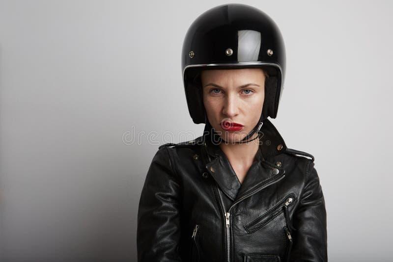 Retrato del primer de la mujer del motorista sobre el fondo blanco, el casco juguetón negro elegante que lleva y la chaqueta de c fotografía de archivo libre de regalías