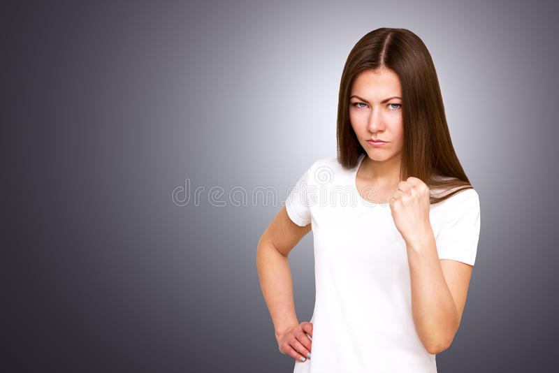 Retrato del primer de la mujer enfadada enojada joven con la mala actitud que da charla al gesto de mano que muestra gris del puñ imagenes de archivo
