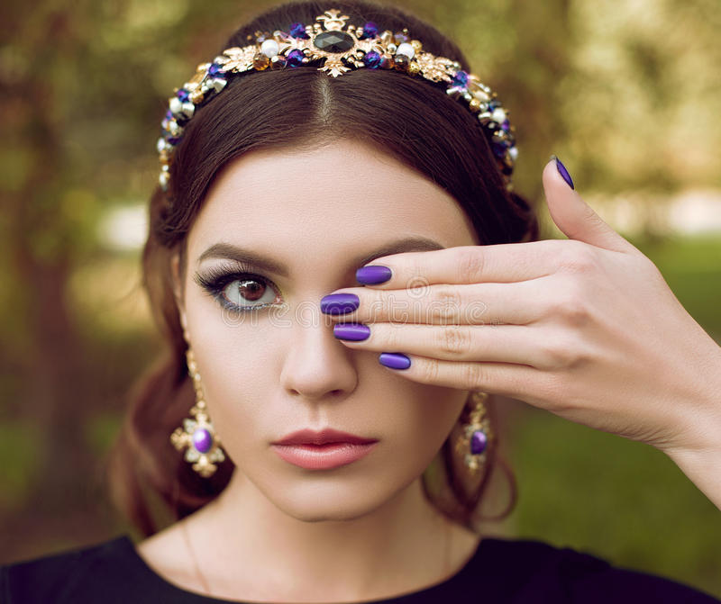 Retrato del primer de la mujer hermosa de la moda con la manicura púrpura brillante, maquillaje elegante La muchacha está llevand foto de archivo