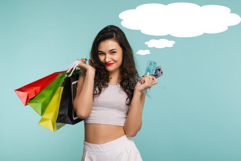 Retrato del primer de la mujer hermosa joven feliz que sostiene la tarjeta de crédito y de los bolsos de compras, mirando la cáma fotografía de archivo