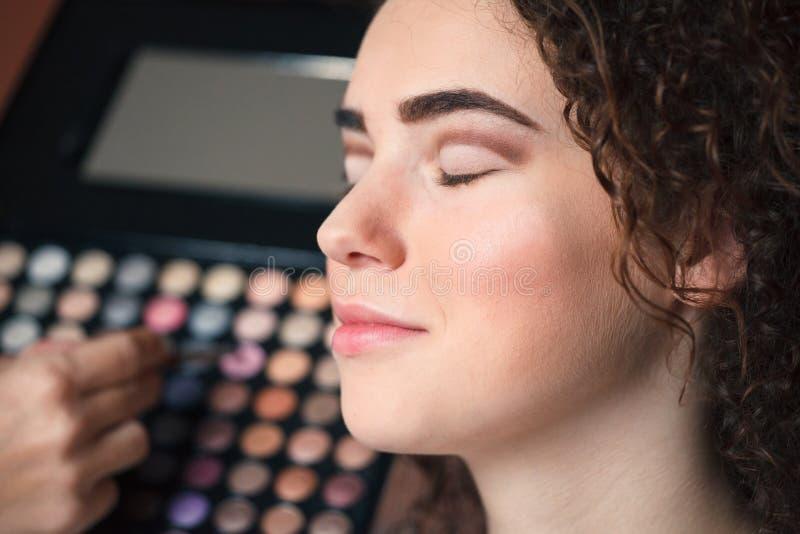 Retrato del primer de la mujer hermosa que consigue maquillaje profesional con el cepillo Belleza y concepto del maquillaje imagen de archivo libre de regalías