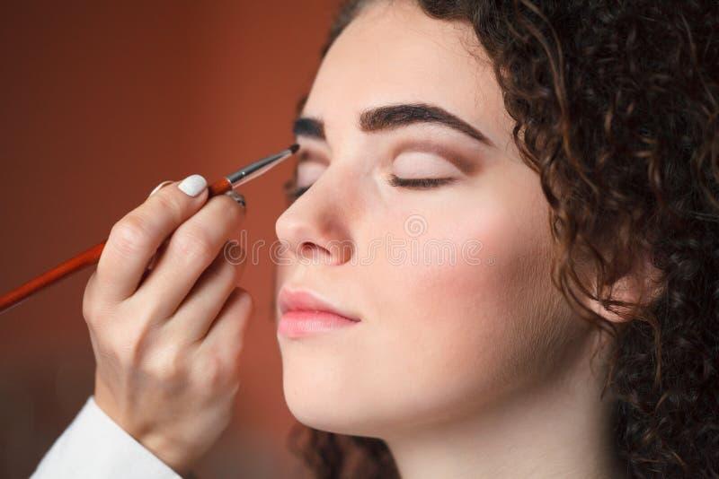 Retrato del primer de la mujer hermosa que consigue maquillaje profesional con el cepillo Belleza y concepto del maquillaje foto de archivo libre de regalías