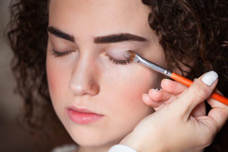 Retrato del primer de la mujer hermosa que consigue maquillaje profesional con el cepillo Belleza y concepto del maquillaje foto de archivo