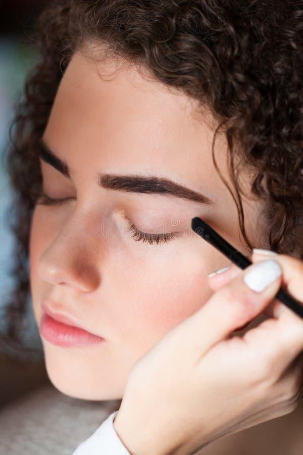Retrato del primer de la mujer hermosa que consigue maquillaje profesional con el cepillo Belleza y concepto del maquillaje fotos de archivo
