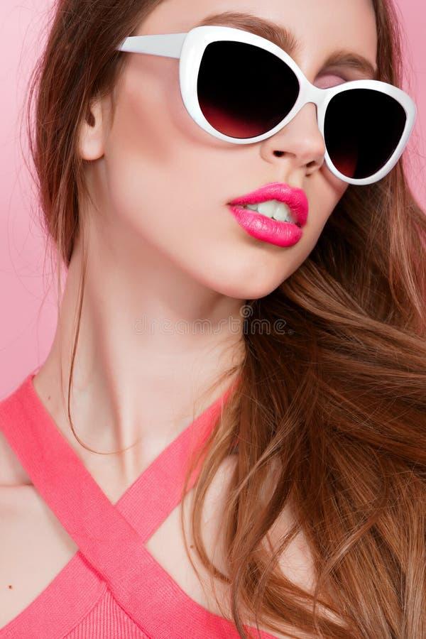 Retrato del primer de la mujer joven atractiva delgada hermosa joven en vestido sexy con los labios sensuales rojos en fondo rosa foto de archivo