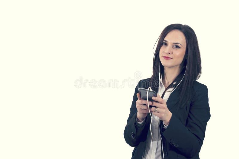 Retrato del primer de la mujer joven preciosa que disfruta de música usando los auriculares, aislado imagen de archivo