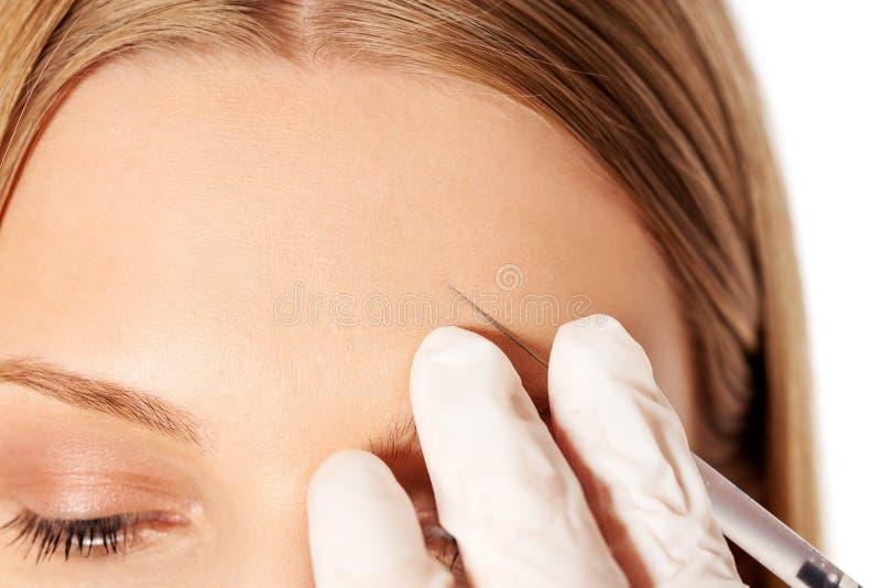 Retrato del primer de la mujer joven que consigue la inyección cosmética con la jeringuilla fotos de archivo