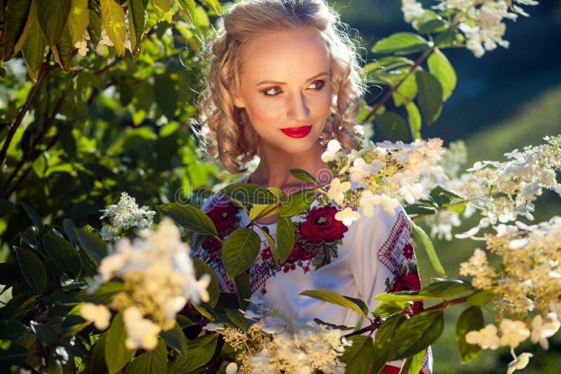 Retrato del primer de la mujer joven rubia atractiva con maquillaje y del peinado rizado en la presentación cerca de arbusto con  fotografía de archivo