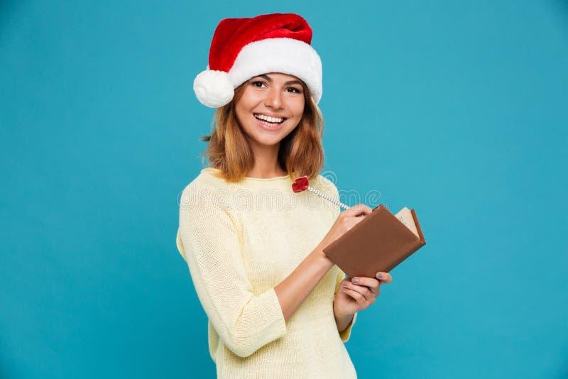 Retrato del primer de la mujer morena alegre en notas de la escritura del sombrero del ` s de Papá Noel mientras que mira la cáma imagen de archivo