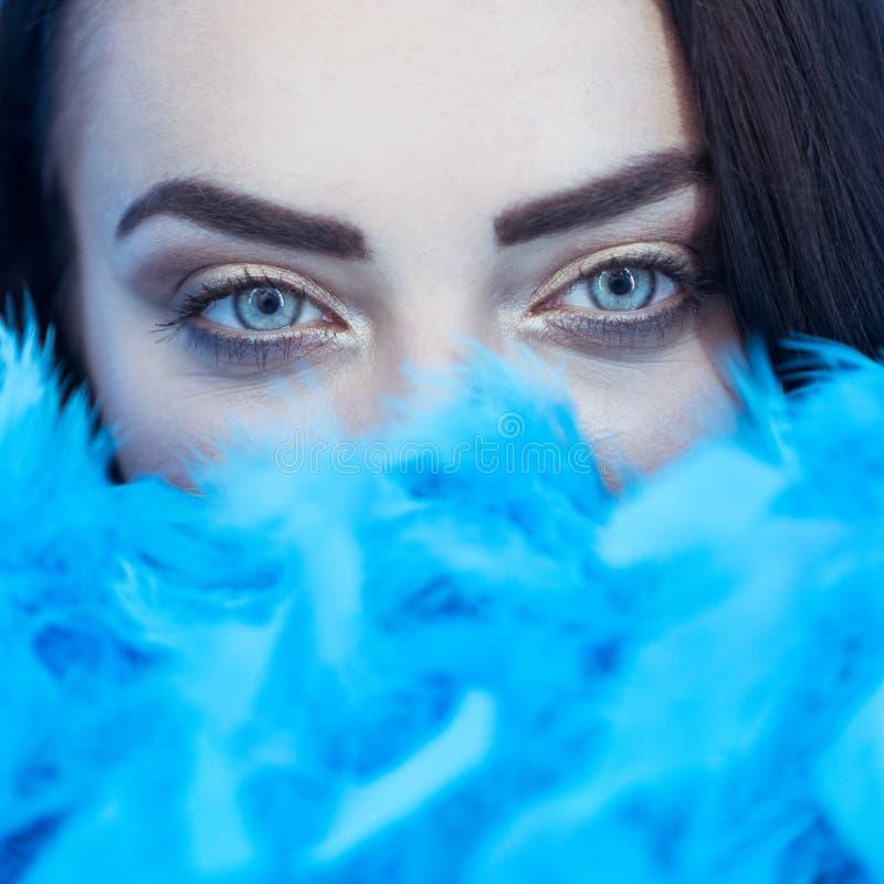 Retrato del primer de la mujer morena atractiva hermosa que sonríe y que mira en la cámara mientras que con la boa de plumas azul fotos de archivo