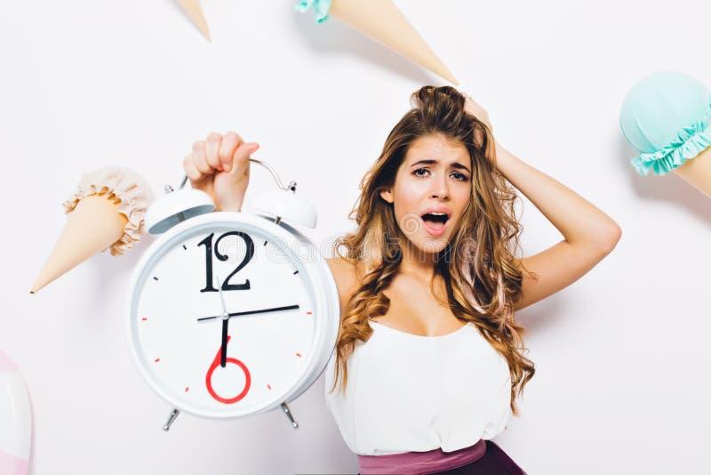 Retrato del primer de la mujer morena consternada en el equipo elegante que toca el pelo y que sostiene el reloj grande Mujer jov imagenes de archivo