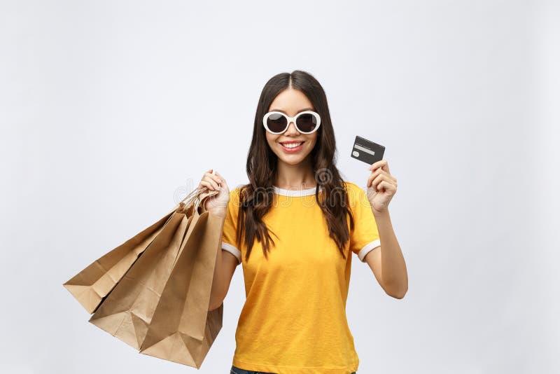 Retrato del primer de la mujer morena joven feliz en las gafas de sol que sostienen la tarjeta de crédito y bolsos que hacen comp imagen de archivo libre de regalías