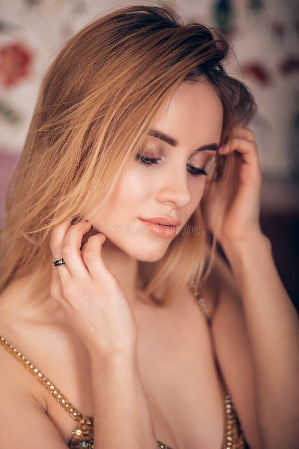 Retrato del primer de la mujer rubia que mira abajo Muchacha hermosa joven con maquillaje profesional, piel limpia y de oro brill fotos de archivo libres de regalías