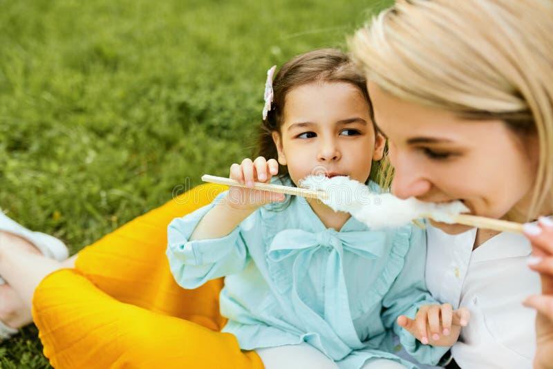 Retrato del primer de la niña que come el caramelo de algodón con su mamá, sentándose en la hierba verde en el parque D?a de madr fotos de archivo libres de regalías