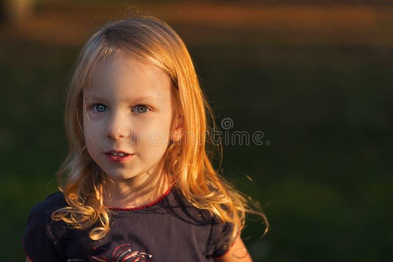 Retrato del primer de la pequeña situación rubia sonriente adorable linda en parque de la caída del otoño, niñez feliz de la much imagenes de archivo