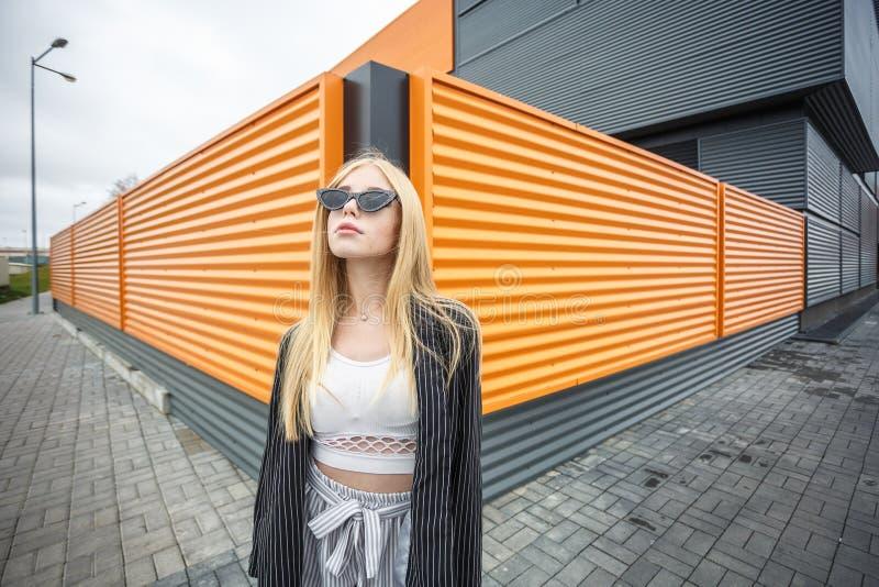 Retrato del primer de la peque?a muchacha modelo sonriente linda en chaqueta rayada y las gafas de sol que presentan cerca de nar foto de archivo libre de regalías