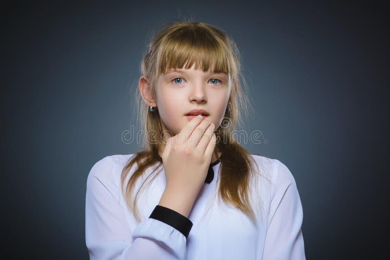 Retrato del primer de la sorpresa que va de la niña en fondo gris imagen de archivo