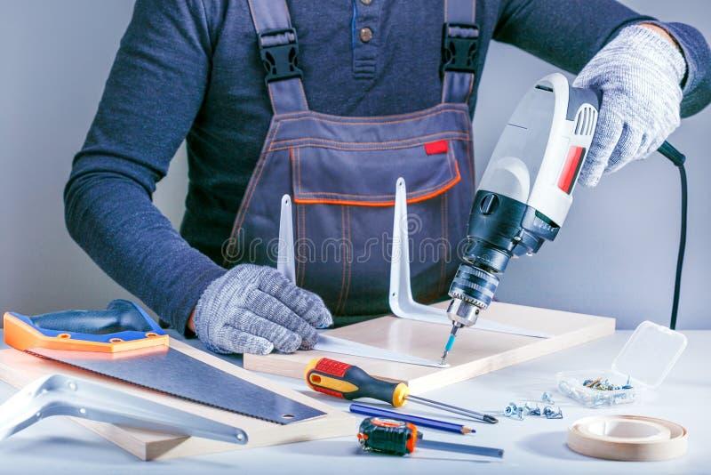 Retrato del primer de las manos masculinas que hacen los muebles en taller de los carpinteros fotos de archivo