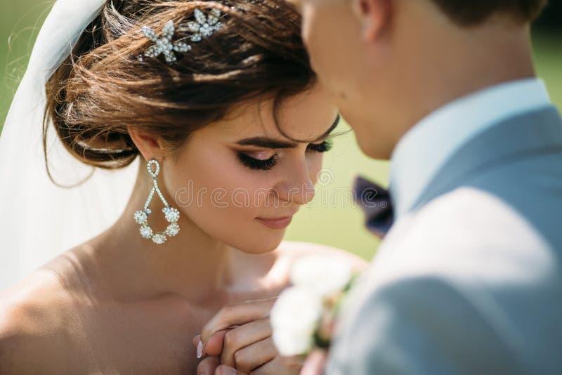 Retrato del primer de recienes casados el día de boda La novia abraza con el novio antes del beso Hombre en traje de negocios y foto de archivo libre de regalías