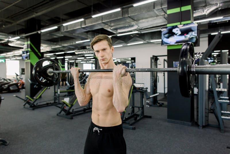 Retrato del primer de un entrenamiento muscular del hombre con el barbell en el gimnasio imagen de archivo libre de regalías