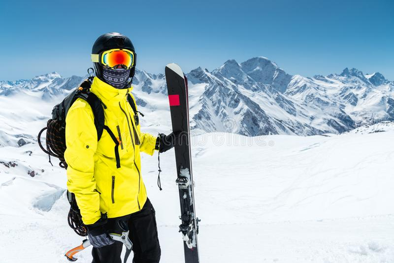 Retrato del primer de un esquiador que lleva un casco protector y los vidrios Una máscara y una bufanda con un hacha de hielo en  foto de archivo libre de regalías