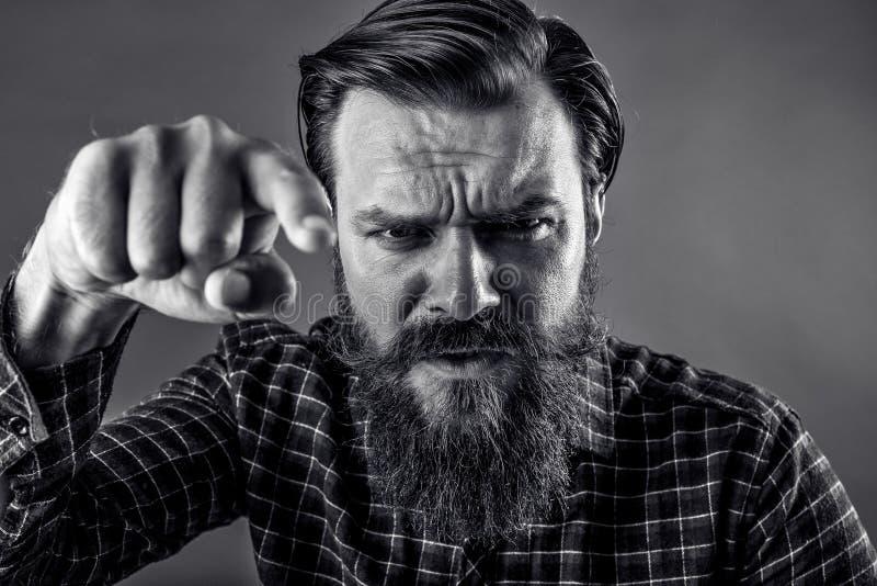 Retrato del primer de un hombre barbudo enojado que amenaza con su fi imagenes de archivo