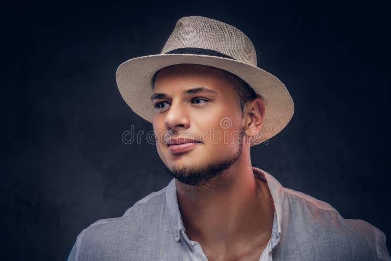 Retrato del primer de un hombre barbudo de moda hermoso en una camisa y un sombrero de Panamá blancos foto de archivo