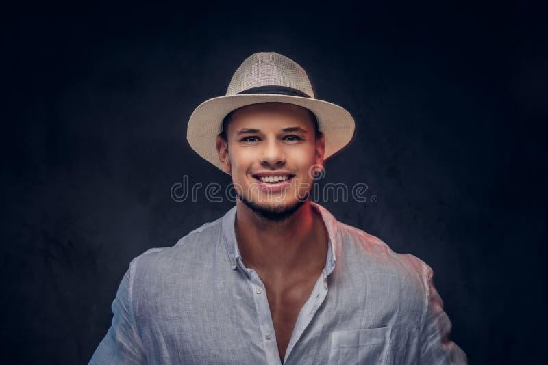 Retrato del primer de un hombre barbudo de moda hermoso sonriente en una camisa y un sombrero de Panamá blancos imagen de archivo