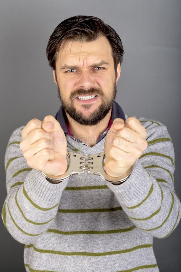 Retrato del primer de un hombre joven con las manos esposadas imagen de archivo