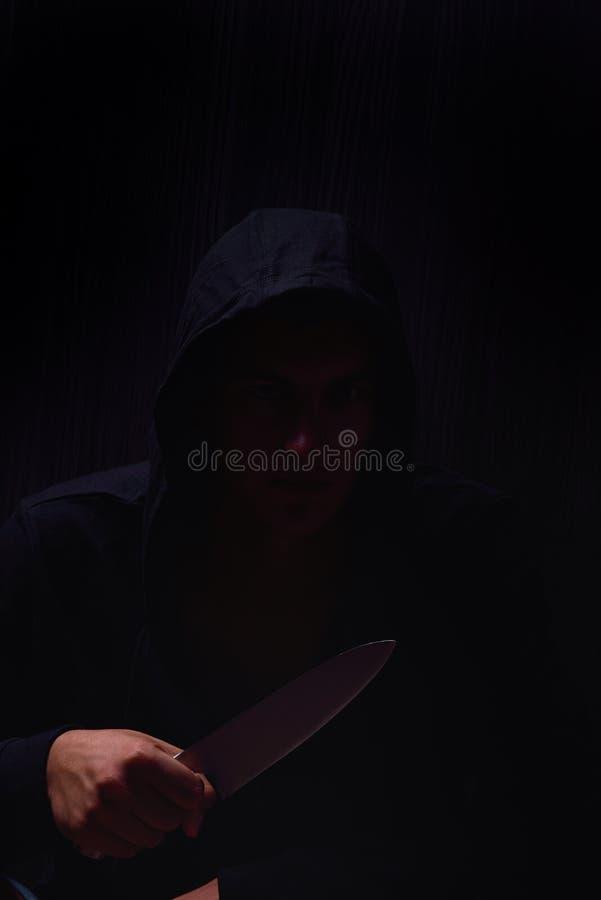 Retrato del primer de un hombre joven en una sudadera con capucha, sosteniendo un cuchillo adentro imagen de archivo